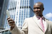 Succesvolle zakenman met behulp van een mobiele telefoon in de stad. — Stockfoto
