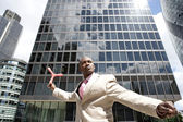 Businessman throwing boomerang while standing in the middle of the financial district. — Foto Stock