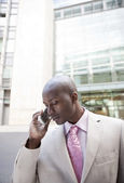 Young businessman talking on a cell phone standing by office building. — Stock Photo