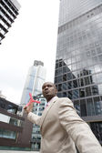 Businessman throwing a boomerang while standing in the middle of the financial district. — Foto Stock