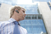 Young businessman using a hands free device to speak on the phone — Stock Photo