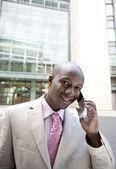 Empresario hablando por un teléfono celular mientras está parado por un edificio de oficinas. — Stockfoto