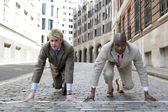 Two businessmen in the ready position to start a race in the financial distric. — Stock Photo