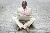 Jonge zakenman met behulp van een laptopcomputer terwijl u zit in het midden van de weg. — Stockfoto