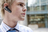 Young businessman using a hands free device to speak on his cell phone — Stock Photo