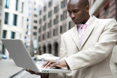Young businessman using a laptop computer in the financial district. — Stock Photo