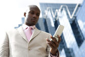 Detail of a cell phone being used by a businessman in the financial district. — Stock Photo