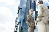 Two businessmen standing by a modern office building. — Stock Photo