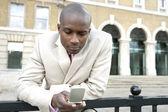 Jonge zakenman tekstberichten op een mobiele telefoon in de stad. — Stockfoto