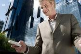 Jeune homme d'affaires en utilisant un téléphone cellulaire lorsque vous êtes debout par un immeuble de bureaux de verre réfléchissant. — Photo