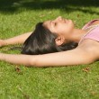 Stock Photo: Young inditeenager laying down on green grass with her eyes closed.