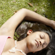 Over head portrait of a indian girl laying down on green grass in the park — Stock Photo #21924963