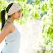 Stock Photo: Profile view of Idigirl standing by lake on sunny golden day.