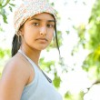 Indian teenager looking at camera with trees foliage in the background. — Stock Photo