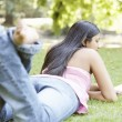 Stock Photo: Indigirl laying down on green grass in park, reading book.