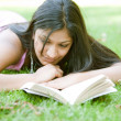 Indigirl reading book while laying down on green grass in park. — Stock Photo #21925059