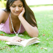 Portrait of an Indian girl reading a book while laying down on green grass in the park. — Foto de Stock