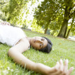 Indian girl laying down on green grass in a park on a sunny day. — Stock Photo #21925099