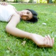 Indian girl laying down on green grass in the park — Stock Photo
