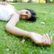 Indian girl laying down on green grass in the park - Stock Photo
