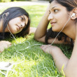 Two indian girls sharing their earphones to listen to music in the park. — Stock Photo