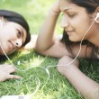 Stock Photo: Two indigirls sharing their earphones to listen to music in park.