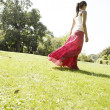 Stock Photo: Young womwalking across park