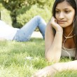 Two indian girls in the park using technology and listening to music. — Stock Photo