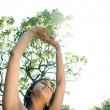 Stock Photo: Young Inditeenager breathing and stretching her arms in air