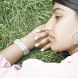 Indian girl's face laying down on grass. — Stock Photo