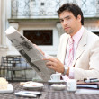 Attractive businessman reading the newspaper while having breakfast — Stock Photo