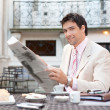 Young attactive hispanic businessman reading the newspaper — Stock Photo #21925707