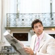 Attractive young businessman reading the newspaper  — Stock Photo