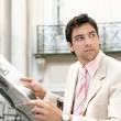 Young businessman reading a newspaper — Stock Photo