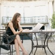 Attractive young businesswoman using a laptop computer while sitting at a coffee shop's terrace table. — Stock Photo
