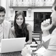 Black and white portrait of three business sharing a table at a coffee shop terrace — Stock Photo