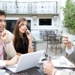 Three business sharing a table at a coffee shop terrace — Stock Photo