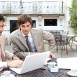 Two busy businessmen having a meeting in a coffee shop terrace — Stock Photo