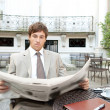 Attractive young businessman reading the newspaper while having a coffee — Stockfoto