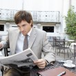 Attractive young professional reading a newspaper while having coffee — Stock Photo