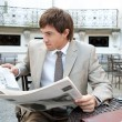 Attractive young businessman reading the newspaper while having a coffee  — Stock Photo