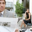 Business sitting in a classic coffee shop terrace using technology and reading the newspaper — Stock Photo