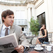 Stock Photo: Businesswoman sitting at coffee shop terrace having a mobile cell phone conversation