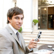 Young attractive businessman using a cell phone while sitting in a hotel coffee shop — Stock Photo