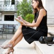 Elegant businesswoman sitting on a classic buildings steps — Stock Photo