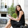 Stock Photo: Elegant businesswomsitting on classic buildings steps taking notes