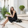 Elegant businesswoman sitting on a classic buildings steps taking notes — Stock Photo #21926293