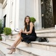 Elegant businesswoman sitting on a classic buildings steps taking notes in her agenda — Foto Stock