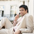 Young attractive businessman smiling and using a cell phone - Stock Photo