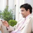 Attractive businessman using his cell phone while sitting on the steps — Stock Photo